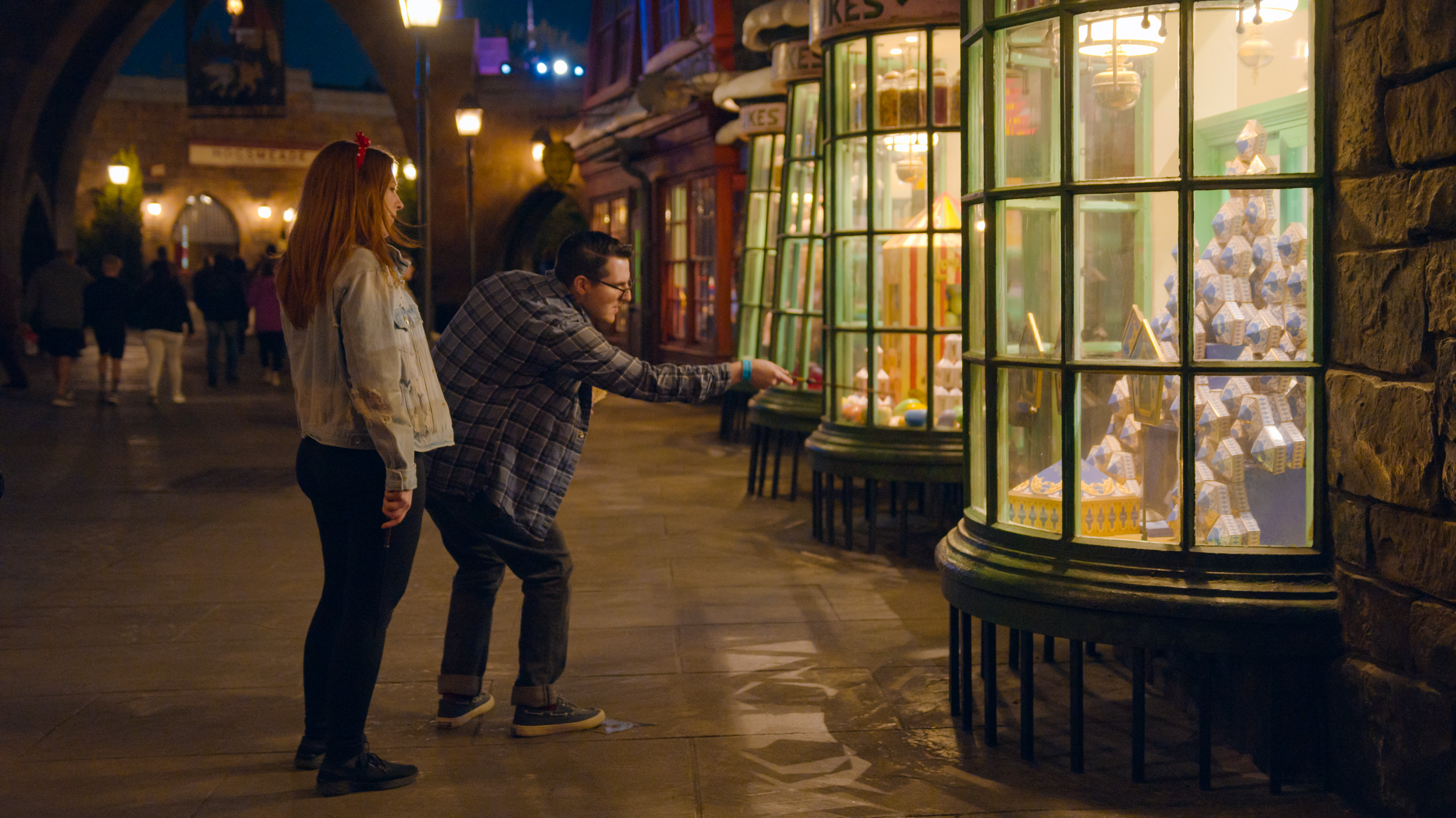 Man waves interactive wand at Harry Potter shop, alongside a woman